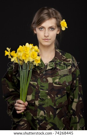 Young female in male military chemise holding bunch of flowers - stock photo