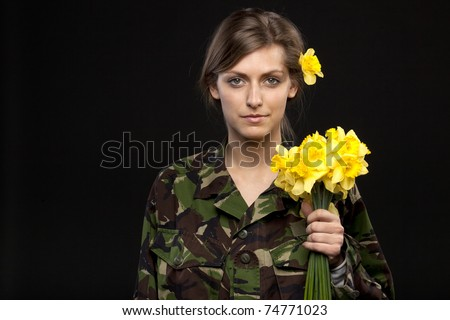 Young female in male military chemise holding bunch of flowers and with a flower over the ear - stock photo