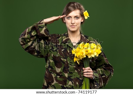 Young female in male military chemise holding bunch of flowers saluting on green background - stock photo