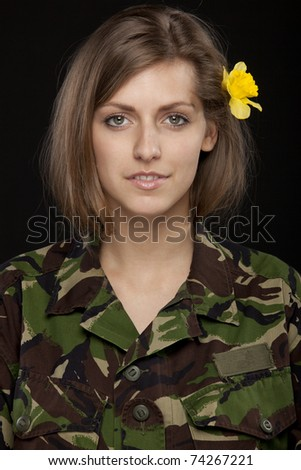 Young female in male military chemise with a flower over the ear - stock photo