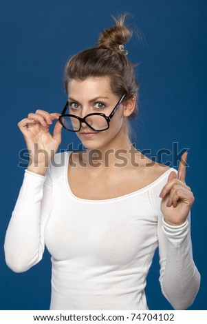Young female in old fashioned eyeglasses pointing with her finger up - stock photo