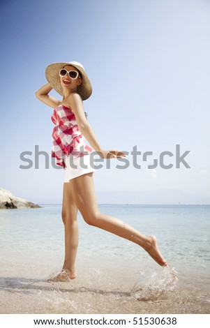young female in retro outfit, jumping around on the beach - stock photo