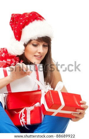 Young female in Santa hat sitting on the floor and unwrapping her Xmas gifts, over white background - stock photo
