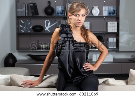 Young female in the home interior looking at camera - stock photo