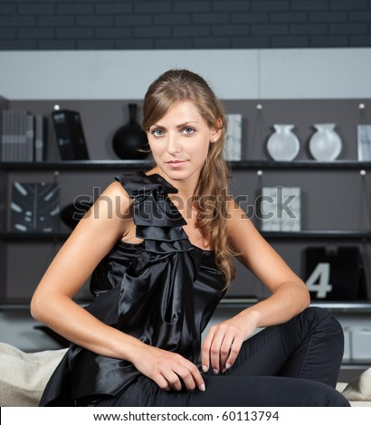 Young female in the home interior looking at camera against bookshelves background - stock photo