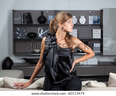 Young female in the home interior looking sideways - stock photo