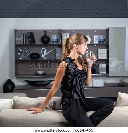 Young female in the home interior with glass of water looking sideways, in the living-room wearing elegant clothes - stock photo