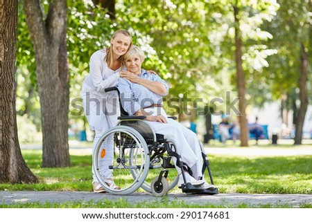 Young female in uniform with senior patient in a wheelchair chilling out in park - stock photo
