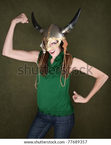 Young Female in Viking Helmet Flexes Her Muscles - stock photo