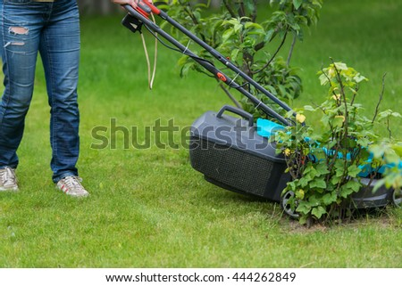 Young female in yard - pushing grass trimming lawnmower - stock photo
