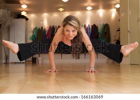 young female in yoga studio doing yoga poses - stock photo