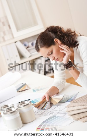 Young female interior designer at office with paint and color swatch