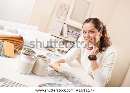 Young female interior designer at office with paint and color swatch - stock photo