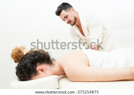 Young female is getting a body massage by handsome man as healthy lifestyle and relaxation concept - stock photo