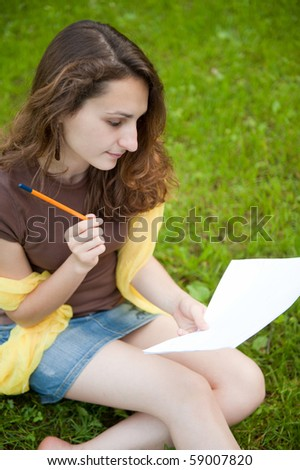 Young female is making notes in college lawn - stock photo