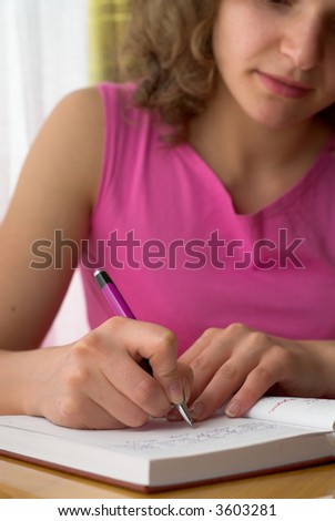Young female is writing notes and planning her schedule. - stock photo