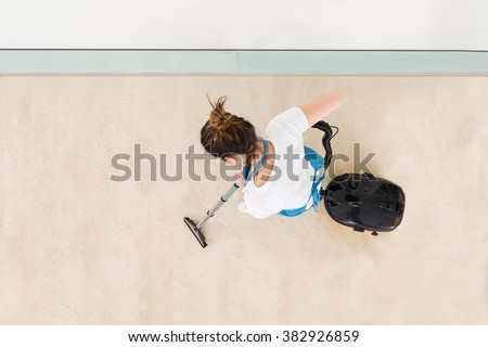 Young Female Janitor In Uniform Vacuuming Floor - stock photo
