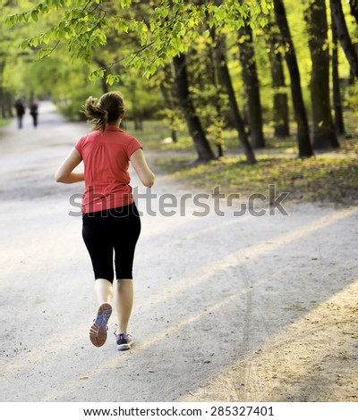 young female jogger exercising in the park - stock photo
