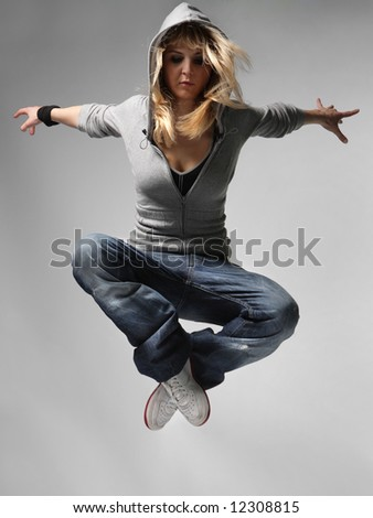 young female jumping on the grey background - stock photo