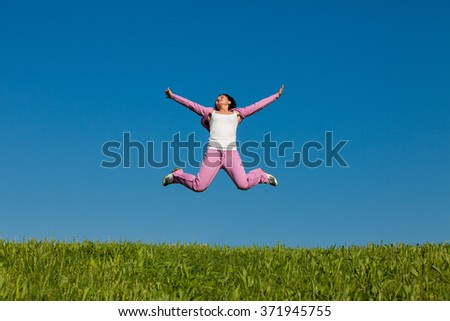 young female jumps in field