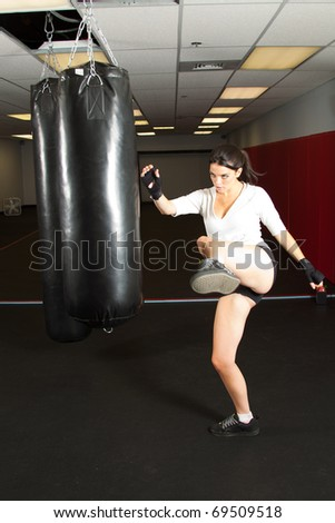 young female kick boxing in a gym - stock photo