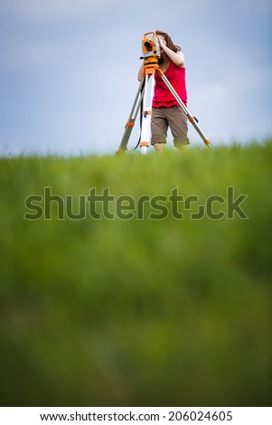 Young, female land surveyor at work - using the theodolite level outdoors - stock photo