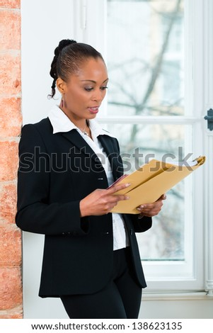 Young female lawyer or businesswoman standing at a window in office reading a file or dossier - stock photo