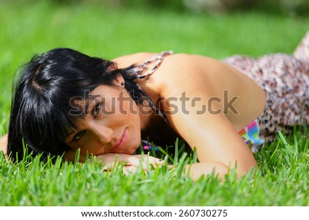 Young female laying on the green grass - stock photo