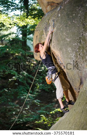 Young female lead climber climbing on large boulder securing carbines and rope. Summer day.