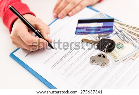 Young female leasing consultant signing car insurance contract in the office. Closeup of sold vehicle key with credit card and cash. Shallow depth of field.   - stock photo
