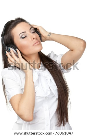 Young female listening to music in headphones isolated on white - stock photo