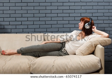 Young female listening to the music in headphones with closed eyes - stock photo