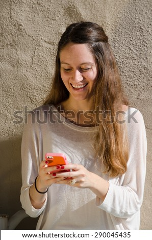 Young female looking at her cell phone, reading a text message