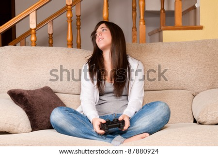 Young female lose playing video-games concentrating on sofa at home - stock photo