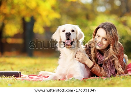 Young female lying down with her labrador retriever dog in a park - stock photo