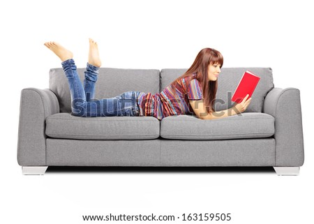 Young female lying on a sofa and reading a book isolated on white background - stock photo
