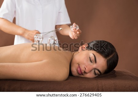 Young Female Lying On Front Receiving Cupping Treatment On Back