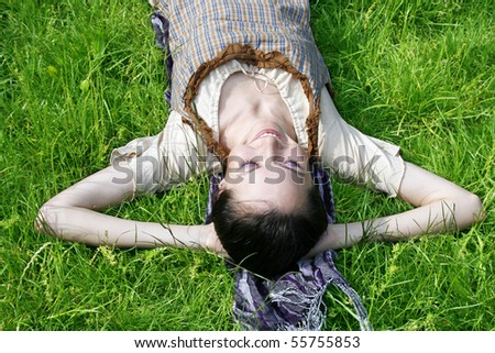 Young female lying on the grass in the park - stock photo