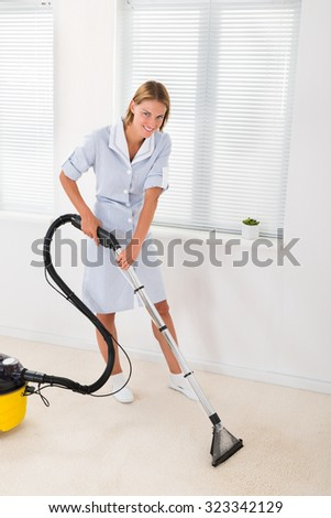 Young Female Maid In Uniform Vacuuming Floor - stock photo
