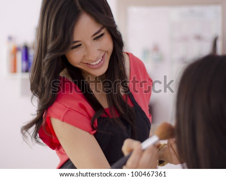 Young female makeup artist applying makeup on a client - stock photo