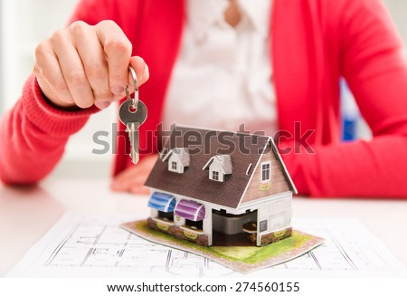 Young female makler holding key of new apartment. Real estate rent and sale concept. Shallow depth of field. - stock photo
