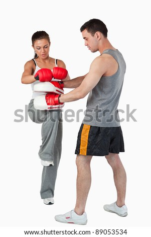 Young female martial arts fighter practicing her knee technique against a white background - stock photo