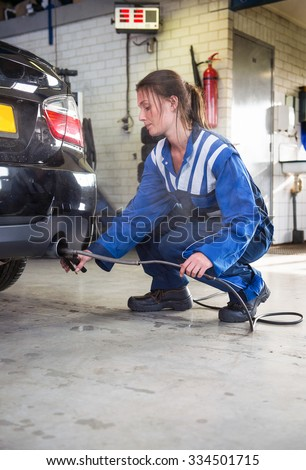 young, female mechanic, checking the diesel exhaust emission rates during a periodic check, using diagnostics equipment, sticking a sensor in the exhaust of a diesel fueled vehicle - stock photo