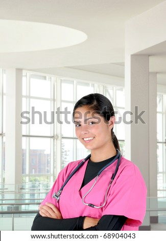 Young female medical professional wearing pink scrubs and stethoscope in modern clinic setting. Woman is smiling with her arms crossed.