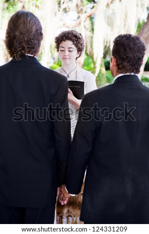 Young female minister marries gay male couple in lovely outdoor wedding ceremony. - stock photo