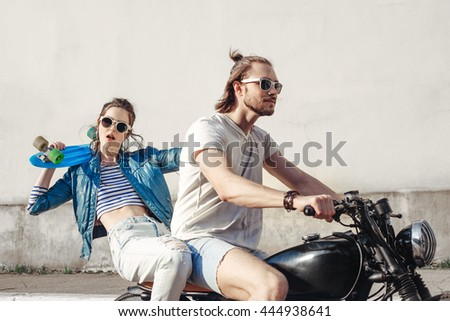 Young female model holding skateboard. Young man and woman having fun on a sunny day