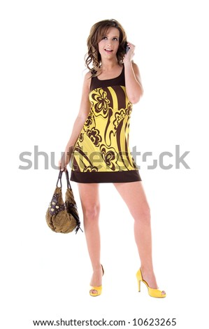 Young female model in a bold floral print mini dress talking on a cell phone - stock photo