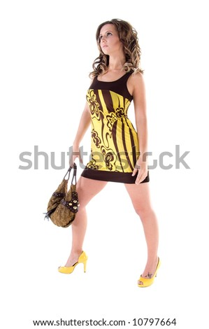 Young female model in a bold floral print mini dress with a big floppy purse - stock photo