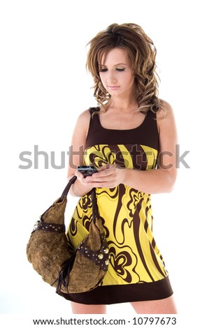 Young female model in a bold floral print mini dress with a big purse over her arm while she types a text message on her phone - stock photo