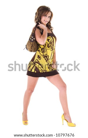 Young female model in a bold floral print mini dress with a big purse over her shoulder - stock photo
